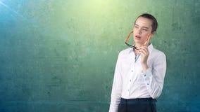 Ritratto sorpreso della donna di affari in gonna bianca su fondo isolato con il divieto dei capelli ed i vetri arancio e neri Immagini Stock Libere da Diritti
