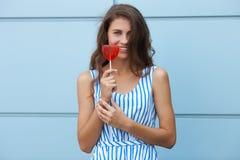Ritratto sorridente all'aperto di giovane bella donna castana felice in vestito a strisce da estate che posa con la lecca-lecca r Fotografie Stock Libere da Diritti