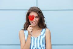 Ritratto sorridente all'aperto di giovane bella donna castana felice in vestito a strisce da estate che posa con la lecca-lecca r Immagini Stock