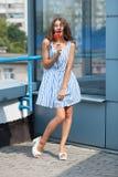 Ritratto sorridente all'aperto di giovane bella donna castana felice in vestito a strisce da estate che posa con la lecca-lecca r Fotografie Stock
