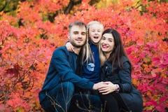 Ritratto sorridente della famiglia felice nella foresta di autunno fotografia stock