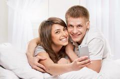 Ritratto sorridente delle coppie che si trovano a letto fotografie stock