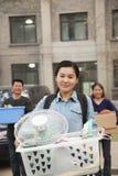 Ritratto sorridente dello studente davanti al dormitorio all'istituto universitario con la famiglia, recipiente di tenuta Immagine Stock Libera da Diritti