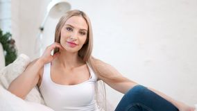 Ritratto sparato medio della donna europea affascinante felice che si siede sullo strato all'interno bianco accogliente video d archivio