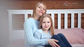 Ritratto sparato medio della madre felice che abbraccia la sua piccola figlia che esamina macchina fotografica stock footage