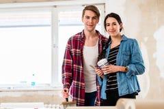 Ritratto strumenti di giovani di tenuta felici delle coppie per il ritocco domestico immagini stock libere da diritti