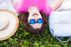 Ritratto superiore della giovane donna che mette sull'erba nel parco Fotografia Stock