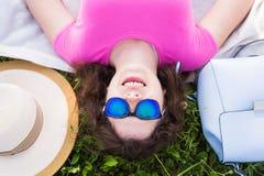 Ritratto superiore della giovane donna che mette sull'erba nel parco Fotografie Stock