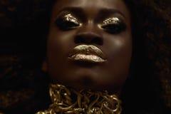Ritratto surreale del grande primo piano del modello femminile afroamericano maestoso con trucco lucido dell'oro Concetto di Vogu immagini stock libere da diritti