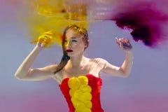 Ritratto surreale di giovane donna attraente con le bolle di aria subacquee in acqua variopinta con inchiostro immagine stock libera da diritti
