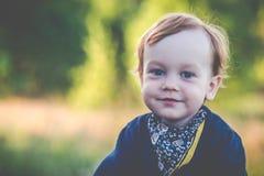 Ritratto sveglio del ragazzo al prato soleggiato fotografie stock libere da diritti
