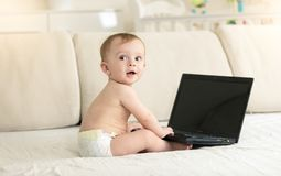 Ritratto tonificato del neonato sveglio che si siede sul sofà e che per mezzo del computer Fotografie Stock