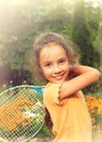 Ritratto tonificato della bambina sveglia che gioca a tennis all'aperto Fotografie Stock