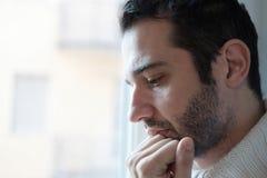 Ritratto triste dell'uomo che guarda dalla finestra fotografia stock