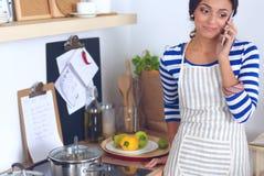 Ritratto un invio di messaggi di testo sorridente della donna delle verdure in cucina a casa immagini stock