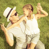Ritratto un padre e una figlia che si siedono sull'erba al giorno t Fotografie Stock Libere da Diritti