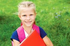 Ritratto un poco della scolara in un vestito blu dalla scuola, con la BO Fotografie Stock