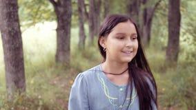Ritratto Una piccola bella ragazza è camminante e sorridente meravigliosamente archivi video