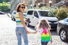 Ritratto urbano del genitore e del bambino La madre e la figlia si tengono per mano, passeggiata intorno alla città, vista poster immagini stock