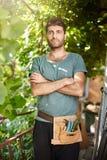 Ritratto verticale di giovane agricoltore dalla carnagione scura barbuto attraente in maglietta blu con tenersi per mano degli st Fotografie Stock Libere da Diritti