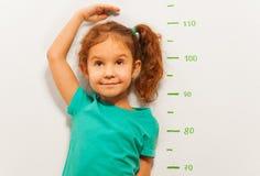 Ritratto vicino di un'altezza di manifestazione della ragazza sulla scala della parete immagini stock libere da diritti
