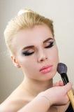 Ritratto vicino di una ragazza con trucco luminoso su un fondo leggero con una spazzola per trucco Fotografie Stock Libere da Diritti