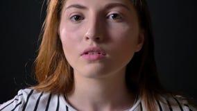 Ritratto vicino donna sicura del giovane zenzero di bella che esamina macchina fotografica, isolato su fondo nero video d archivio