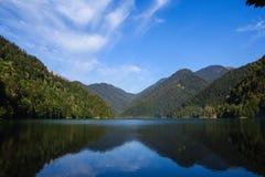 Ritsa湖包围与用森林盖的高加索山脉 免版税库存图片