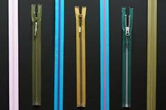 Ritssluitingen voor kleren op zwarte Stock Fotografie