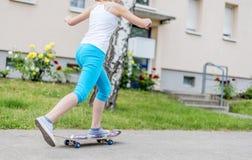Ritt för flickatonåringutbildning på en skateboard Arkivfoto