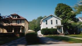 Ritt längs typiska amerikanska förorter Från fönstret av bilen kan du se trähus och propra gräsmattor arkivfilmer
