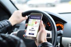 Rittaktiechaufför i bil genom att använda rideshareappen i mobiltelefon arkivfoton