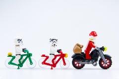 Ritten för stormtrooperen för Lego stjärnakrig en cykel följer en motorcykel av Lego Santa Claus Royaltyfri Fotografi