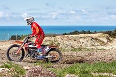 Ritten van de Moto de extreme motorfiets door de modder tegen de achtergrond van de overzeese kust royalty-vrije stock fotografie