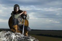 Ritter, der auf einem Felsen sitzt Stockfotografie