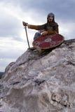 Ritter, der auf einem Felsen sitzt Stockbild