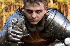 Ritter, der Klinge in einem Wald hält. Stockfotos