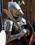 Ritter in der Rüstung mit Schild und Klinge Stockfotografie