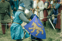 RITTER WEG, MOROZOVO, APRIL 2017: Festival of the European Middle Ages. Medieval joust knights in helmets and chain mail battle on. Swords with shields in their stock photography