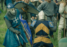 RITTER WEG, MOROZOVO, APRIL 2017: Festival of the European Middle Ages. Medieval joust knights in helmets and chain mail battle on. Swords with shields in their royalty free stock image