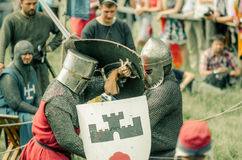 RITTER WEG, MOROZOVO, APRIL 2017: Festival of the European Middle Ages. Medieval joust knights in helmets and chain mail battle on. Swords with shields in their royalty free stock photography