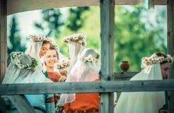 RITTER WEG, MOROZOVO, EM ABRIL DE 2017: As meninas bonitas nos vestidos longos com o véu no weave principal envolvem-se na cabeça Imagem de Stock