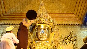 Ritual commences monks wash the face and brush the teeth of the Buddha image stock video footage