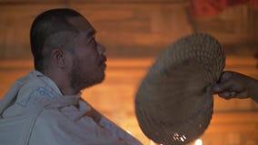 Ritual de la cura en casa mágica Fan que sopla de la bruja al hombre enfermo mientras que cura ceremonia Tradiciones auténticas é almacen de metraje de vídeo