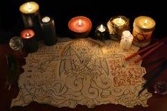 Ritual för svart magi med demonmanuskript- och ondskastearinljus Royaltyfri Foto