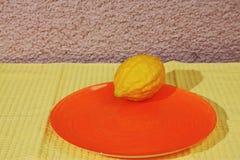 Ritual fruit - citron on orange plate. And yellow napkin. Jewish holiday of Sukkot Royalty Free Stock Photo