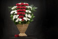 Ritual funeral basket with flowers on a black background. The flower arrangement of the flowers in the basket is used for funerals and bookmarks. Mourning card stock photos