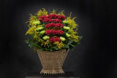 Ritual funeral basket with flowers on a black background. The flower arrangement of the flowers in the basket is used for funerals and bookmarks. Mourning card stock images