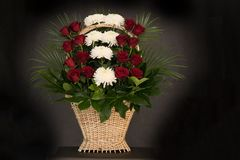 Ritual funeral basket with flowers on a black background. The flower arrangement of the flowers in the basket is used for funerals and bookmarks. Mourning card stock image