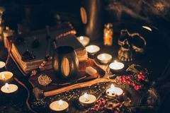 A ritual halloween witchcraft scene with candles, spider web, vintage bottles on the rustic background with a scary skull f. A ritual halloween witchcraft scene stock photography